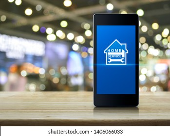 Hammer and wrench with house icon on modern smart mobile phone screen on wooden table over blur light and shadow of shopping mall, Business home service online concept