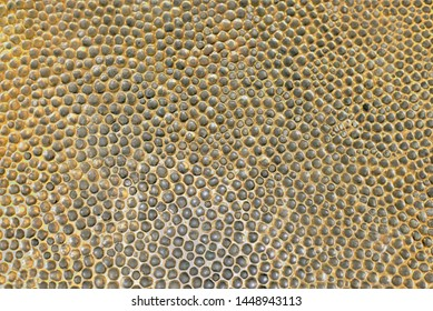 Hammered bronze with chased pattern as background or texture.  Metal gold relief.