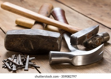 Hammers and a batch of nails lying on a wooden vintage table