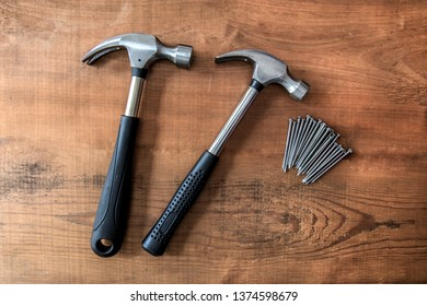 Hammers and nails on wooden background