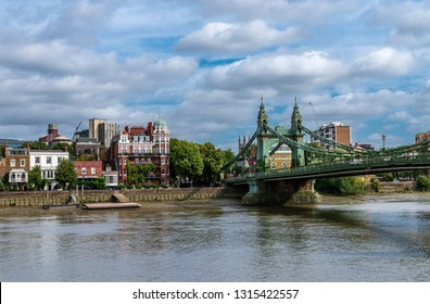 The Hammersmith Bridge, a suspension bridge that crosses the River Thames in west London. Hammersmith is in the background, photo taken from Barnes.