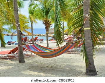 Hammock hanging between palm trees on Curacao beach