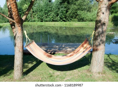 The hammock hanging between pines by the artificial pond in Lithuanian village.