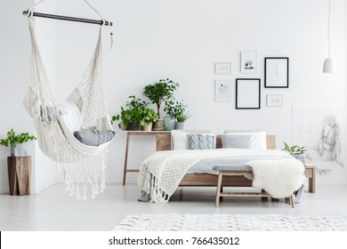 Hammock hanging in bright bedroom with potted plants, woolen coverlet on the bed and posters on white wall