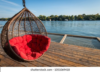 Hammock hanging chair with big red pillow and river scenic