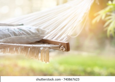 Hammock with lace cushion and newspaper in the garden. Relaxing time in a hammock on a nice summer day.