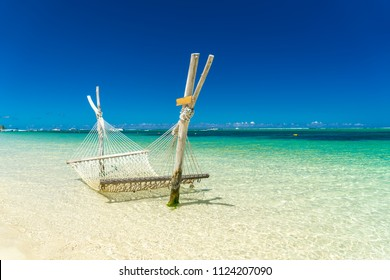 A hammock on the beach against a background of clouds, the ocean and an incredible sky