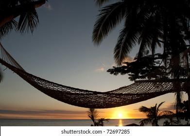 hammock on beach at sunset in Fiji Islands