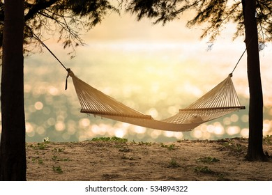 Hammock on the beach at sunset with glowing bokeh from blue sea. Empty white hammock with sunhat and sunglasses in the shade between pine trees on tropical beach