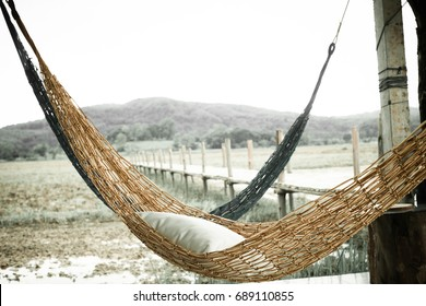 Hammock on the rice field after harvested, mountain background, vintage style.