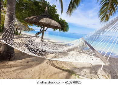 Hammock on tropical beach with palm leaf thatch roofing umbrellas and palm trees in the background
