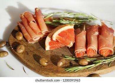 hamon, jamon, jamón .spanish bacon with grapefruit, olives and rosemary. authentic. Spanish national delicacy, uncooked pork ham.