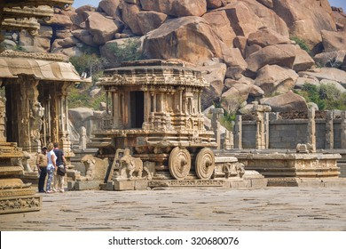 HAMPI, INDIA - 30 FEB 2015: Stone chariot in courtyard of Vittala Temple. Tourists admire the ancient chariot in Hampi, Karnataka, India.  Ruins of Hampi are a UNESCO World Heritage Site.