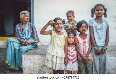 HAMPI, INDIA - 31 JANUARY 2015: Indian family members standing in front of house. Grandmother overlooks five granddaughters. Post-processed with grain, texture and colour effect.
