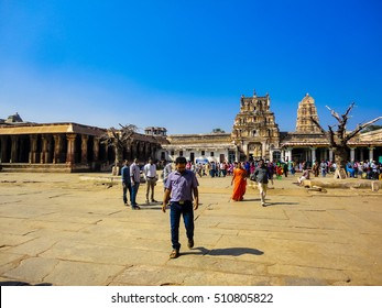 HAMPI, INDIA - DECEMBER 30, 2013: Unidentified people by Virupaksha temple in Hampi, India. Temple is part of the Group of Monuments at Hampi, designated a UNESCO World Heritage Site