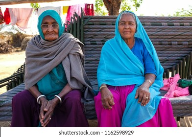 HAMPI, INDIA - FEBRUARY 14, 2015: Two elderly Indian women dressed in traditional clothes and head scarf sitting on stacked benches.