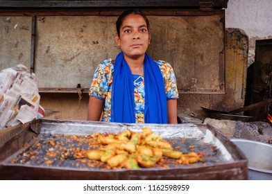 HAMPI, INDIA - JANUARY 27, 2015: Portrait of young Indian woman selling pakora on street stall in India.