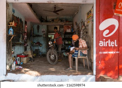 HAMPI, INDIA - JANUARY 27, 2015: Sikh man and young boy in a small improvised garage repair shop.