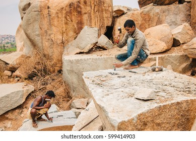 Hampi, India - March 1, 2016: Mining workers manually excavating stone with hammer in Karnataka state of India. Daily life of indian craftsman