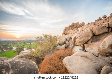 Hampi, Karnataka / India - 02 20 2016: People sitting amongst the rocks at a popular place to watch the sunset in Hampi.