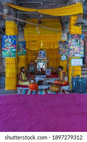Hampi, Karnataka, India - November 5, 2013: Malyavanta Raghunatha Temple. 2 priests sit and chant constantly while playing drums. Purple carpet in front and lots of yellow garlands.