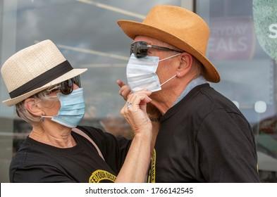 Hampshire, England, UK. 2020. Elderly couple during Covid-19 wife adjusting her husband's mask before entering a shop.