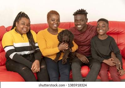 Hampshire, UK. circa 2019. Family portrait with a black Poddle pet dog
