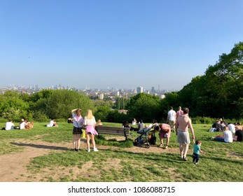 HAMPSTEAD HEATH, LONDON - MAY 6, 2018: People view the city skyline from Parliament Hill on Hampstead Heath in Hampstead, North London, UK.