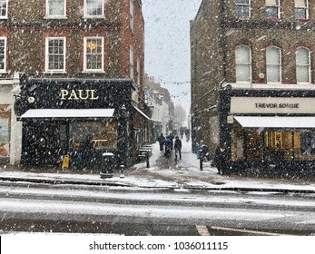 HAMPSTEAD, LONDON - FEBRUARY 28, 2018: Pedestrians navigate snow covered pavements on the high street in Hampstead, North London, UK.