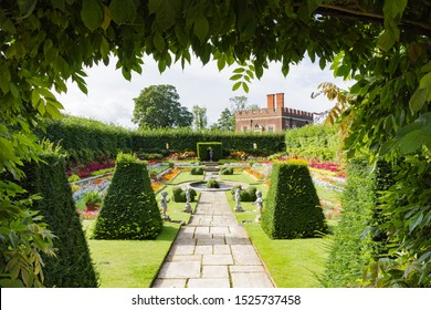 Hampton Court Palace sunken gardens framed by green bushes seen with William III's Banqueting House of 1700 in background