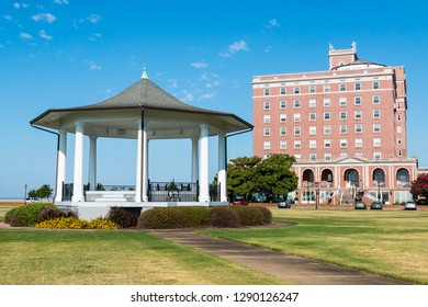 HAMPTON, VIRGINIA - JULY 9, 2017:  The gazebo in Continental Park on the grounds of Fort Monroe, along with the Chamberlin, a historic former hotel built in 1928.