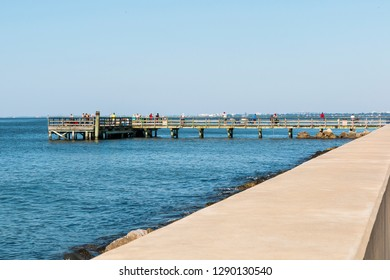 HAMPTON, VIRGINIA - JULY 9, 2017:  People fish on Engineer Pier along the Chesapeake Bay at Fort Monroe.  Engineer Pier is the only designated fishing location at Fort Monroe.