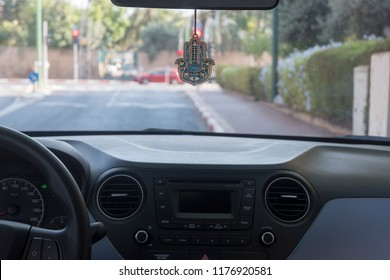 Hamsa hand amulet hanging in the car, due to belief of Jewish people about good luck.