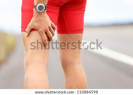 Hamstring sprain or cramps. Running sports injury with male triathlete runner.