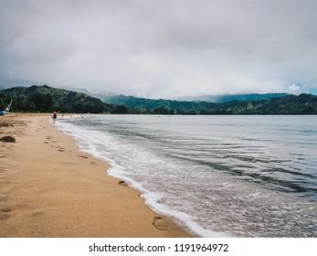 HANALEI BAY, HAWAII - AUGUST 10, 2018: Woman walks down beach in Hanalei Bay, Kauai on overcast day