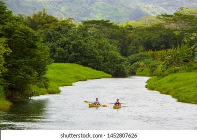 Hanalei, Hawaii - 3/29/2009: A man and woman in kayaks in a stream on the north shore of Kauai near Hanalei, Hawaii