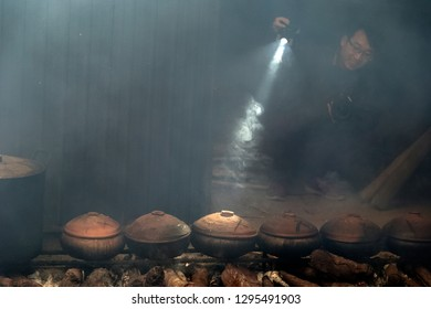 HANAM, VIETNAM January 26, 2019: Workers cook fish with a clay pot. This is the famous method of processing fish of Vietnam.