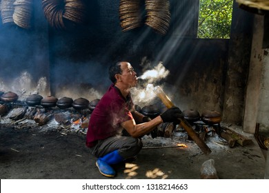 HANAM, VIETNAM January 26, 2019: workers smoke in the area of cooking fish with clay pot. This is how to smoke through a unique and famous bamboo section of Vietnam.