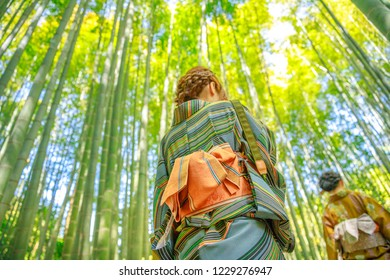 Hanami in spring season with unidentifiable women with green Japanese kimono in bamboo grove of Take-dera Hokoku-ji Temple at sunset in Kamakura, Japan city. Japanese culture and lifestyle.