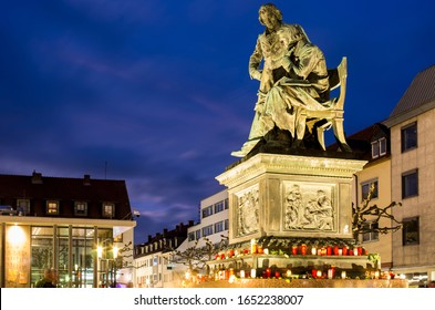 Hanau, Germany - February 20 2020: Flowers & Candles at National memorial statue of famous Grimm Brothers in the city center in Hanau, Germany. Terrorist attack. Right extremism. Mass shooting.
