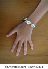 Hand of a 8-year-old girl with a bracelet made with conch shell and straw on a wood surface
