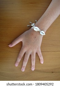 Hand of a 8-year-old girl wearing a bracelet made with conch shell and straw on a wood surface