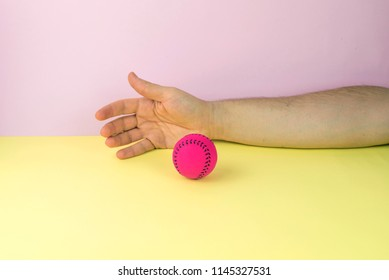 Hand about to capture a pink fuchsia tennis ball on a yellow and pink background. Or hand that has just released a fuchsia pink tennis ball on a yellow and pink background.