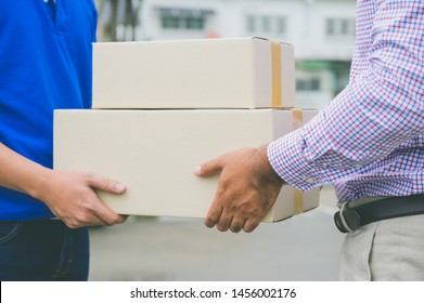 Hand accepting a delivery of boxes from deliveryman.