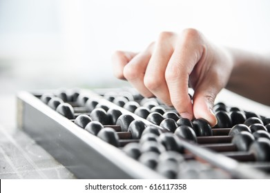 Hand accounting with old abacus for calculation