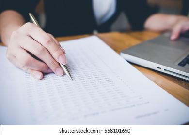 Hand accounts of women holding pen Asian financial calculations.