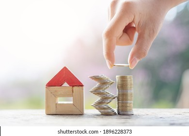 Hand add coin to coin stack. Property investment and house mortgage financial concept,