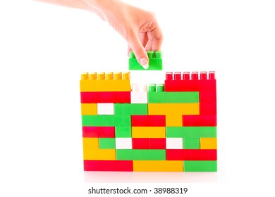 hand add toy brick to toy building isolated on white