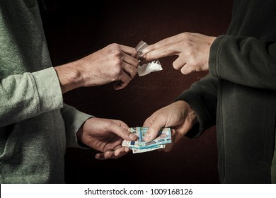 Hand of addict man with money buying dose of cocaine or heroine or another narcotic from drug dealer. Drug abuse and traffic concept.
