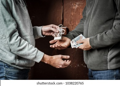 Hand of addict man with money buying dose of cocaine or heroine. Drug abuse and traffic concept